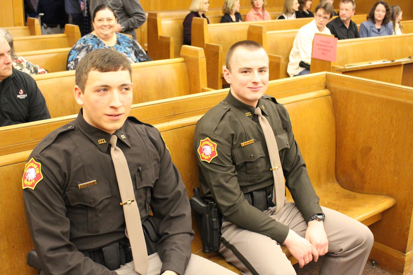 officers seated at the front of the courtroom