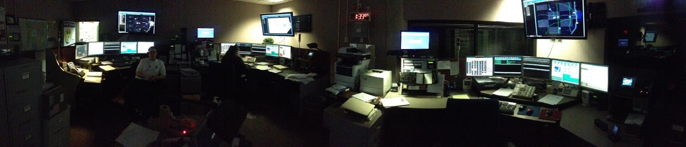 Panoramic shot of the Communications Center - Desks filled with screens, phones, and blinking lights