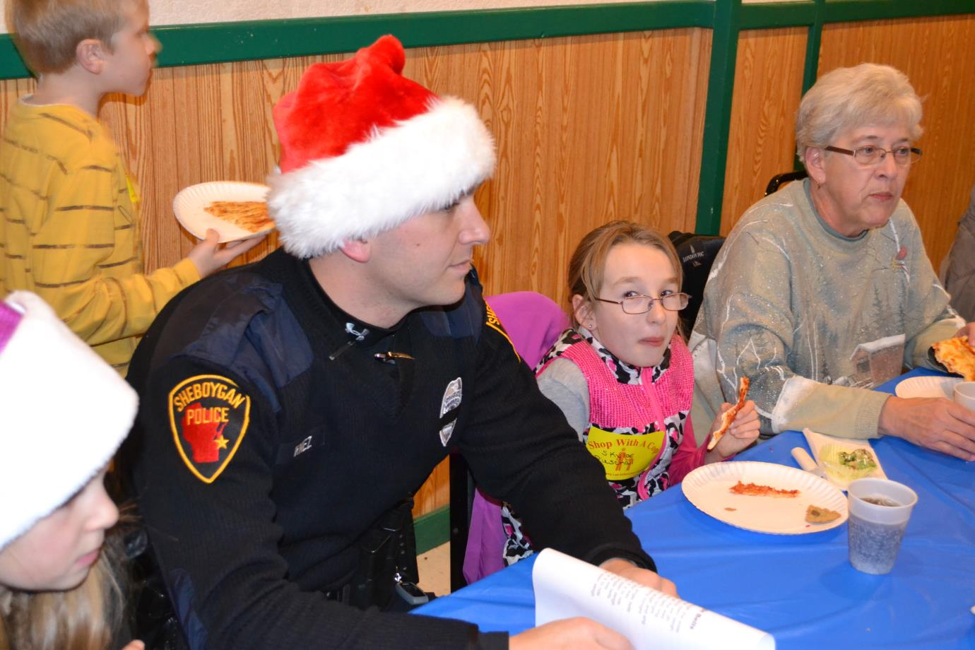 Officer wearing Santa hat while girl nearby laughs