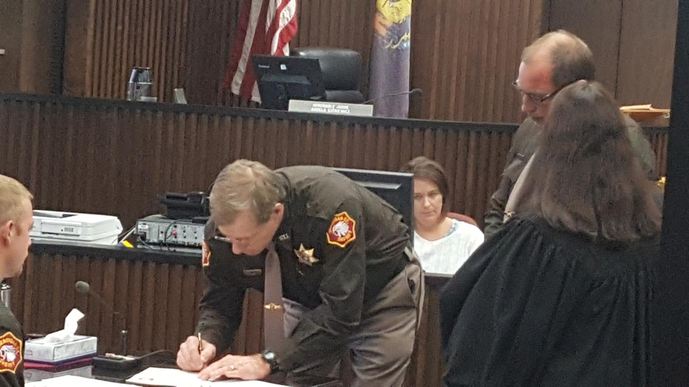 officer signing documents in the courtroom
