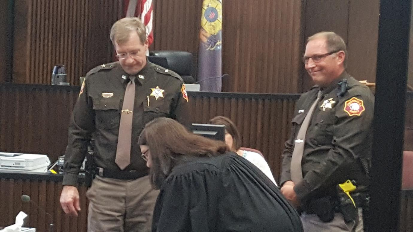 Judge and Sheriff complete paperwork in the courtroom