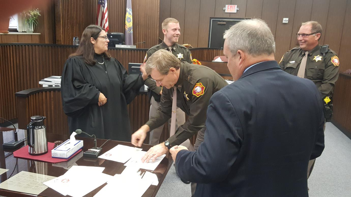 officer reviews documents in the courtroom