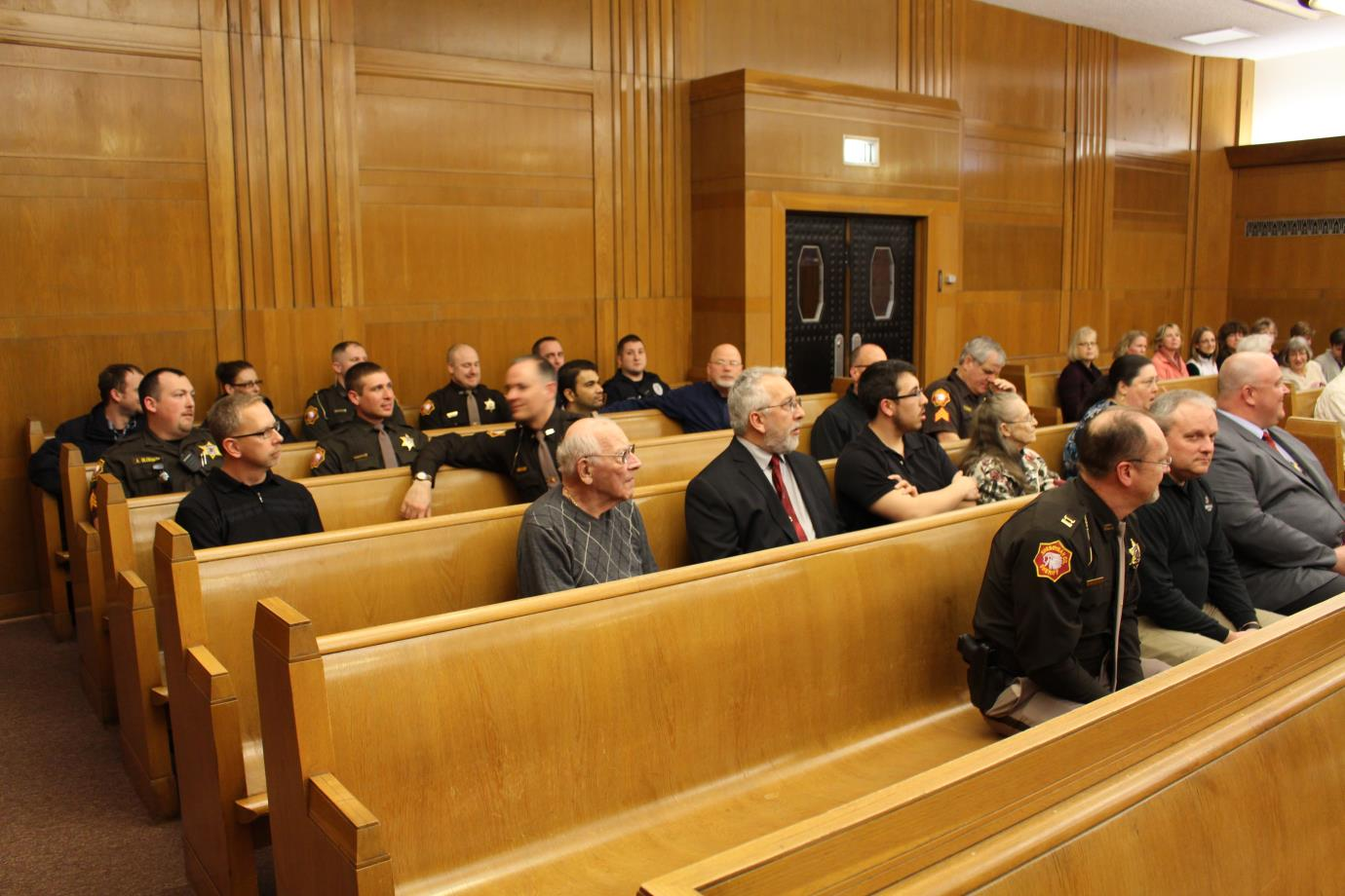 Courtroom seats filled with officers and other attendees